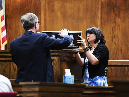 Cindy Coxie, the mother of one of Todd Kohlhepp's victims, shows photos of her son to the judge on Wednesday, July 11, 2018.