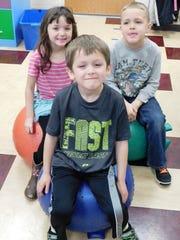 Kindergarteners Alex Simon, front, Teann Greene, back left,  and Daniel Gowitzka showoff their ball seats in Aubrey Baur's class.