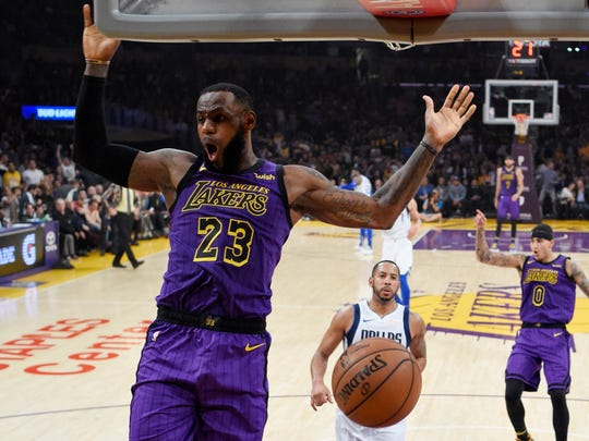Los Angeles Lakers forward LeBron James comes down after a dunk as Dallas Mavericks guard Devin Harris, center, watches along with Lakers forward Kyle Kuzma during the first half of an NBA basketball game Friday, Nov. 30, 2018, in Los Angeles. (AP Photo/Mark J. Terrill)