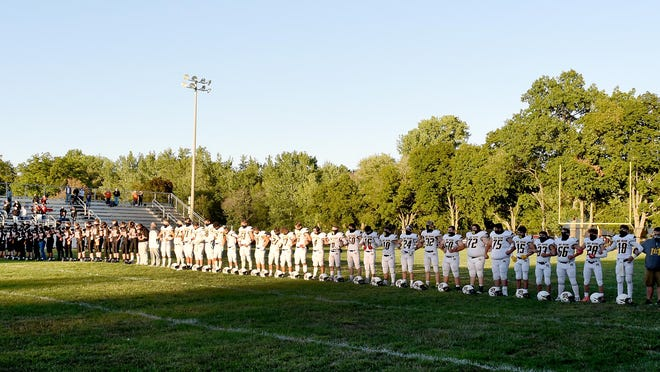 The Summerfield Bulldogs and the Erie Mason Eagles lock arms for the national anthem during the first game of the season Friday night .