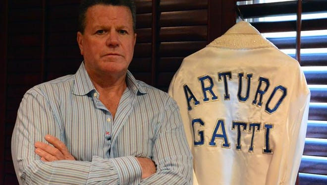 Pat Lynch poses with an Arturo Gatti robe in his Middletown home.