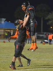 Zachary Brasher lifts John Smith into the air to celebrate