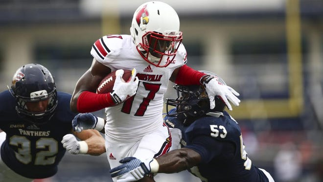 Florida International's Anthony Wint (53) stops Louisville's James Quick (17) during the first half of an NCAA college football game in Miami, Fla., Saturday, Sept. 20, 2014. (AP Photo/J Pat Carter)