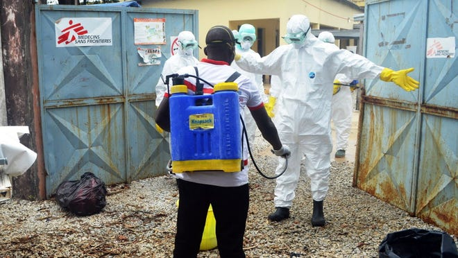 Guinea's Red Cross workers prepare to handle the body of an Ebola victim in Conakry on Sunday.