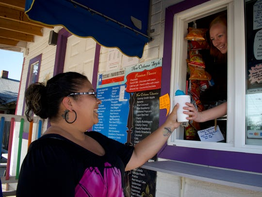 A customer receives her snow cone at Twisted Ice located