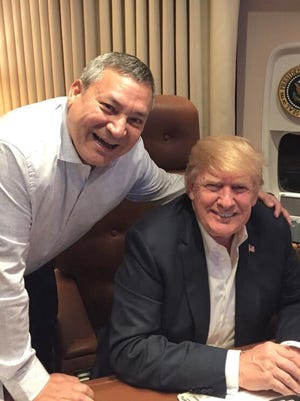 In this June 2018 file photo, former Republican Gov. Eddie Calvo meets President Donald Trump on Air Force One during the president's brief stop on Guam.