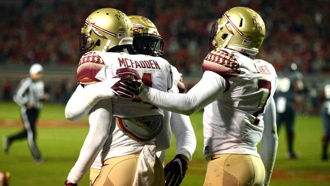 Florida State Seminoles defensive back Tarvarus McFadden (4) is congratulated by teammates after an interception during the first half against the North Carolina State Wolfpack.