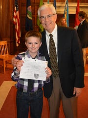Ethan Martin, 12, clutches a drawing of his dream home as he stands with Lt. Gov. Mike Cooney.