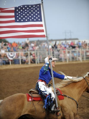 A member of the Chicks-n-Spurs Drill Team rides with the American flag during a rodeo event on June 30, 2012.
