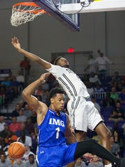 IMG Academy's Trevon Duval, bottom, scores against Mariner High School's Jahmel Myeduring play Friday at the Culligan City of Palms Classic at the Suncoast Credit Union Arena in Fort Myers.