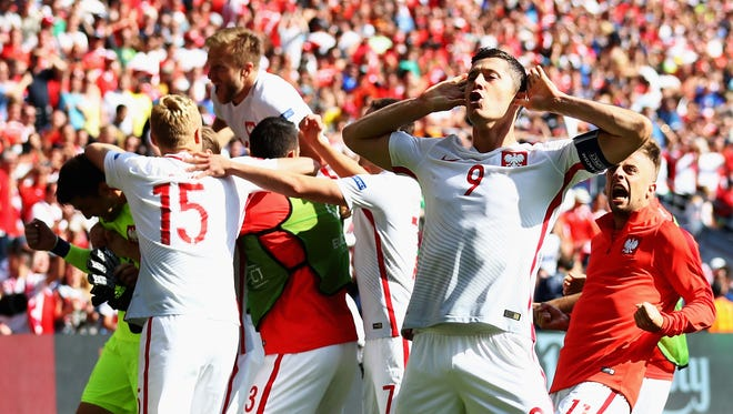 Robert Lewandowski and Poland players celebrate their win in front of the Switzerland supporters.