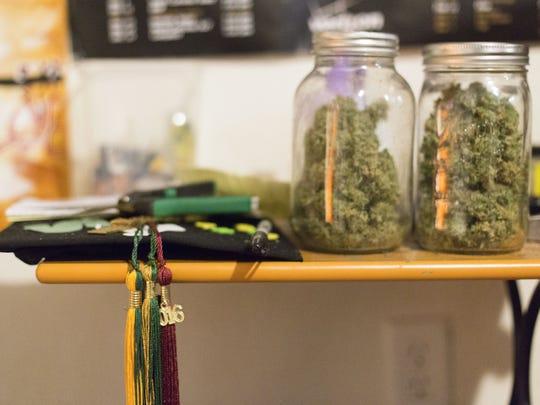 Graduation caps and jars of homegrown medical marijuana sit on Treyous Jarrells' nightstand on Wednesday, June 1, 2016.