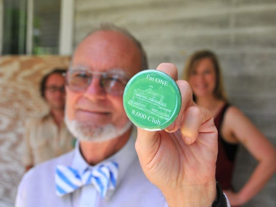 John Daly, president of Green Gables at Historic Riverview Village, Inc. displays an 8,000 Club fundraising button on the home's porch while board members Tony Colomberti and Amy Roadarmel stand in the in background.
