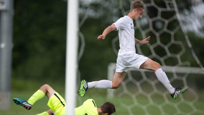 Ankeny Centennial High School's Nermin Kremic jumps past Cedar Rapids Prairie keeper Alec Balta Thursday, June 4, 2015, during the IHSAA State Soccer Championships at Cownie Soccer Park in Des Moines.