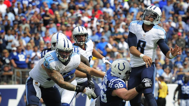 Titans quarterback Marcus Mariota (8) gets a pass off as he is hit by Colts defensive end Henry Anderson (96) at Nissan Stadium on Sunday Sept. 27, 2015, in Nashville, Tenn.
