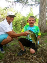 Camp fishing guide Sterling Marschall poses with a Promises for Families camper.