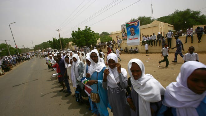 Sudanese women stand in line as they wait for officials' convoys to cross to attend a ceremony to declare an end to 13 years of conflict in Darfur on Sept. 7, 2016 in the North Darfur state capital El-Fasher. Khartoum has repeatedly sought to declare an end to the conflict in Darfur this year, claiming that an April referendum backing the current five-state division of the region turned the page.