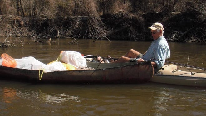 A paddler helps collect trash at a previous Shore Cleanup. This year's event is Saturday.