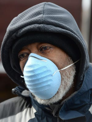 Robert Chandler, 70, of Erie, walks to a bus stop at the intersection of West 18th and State streets in Erie on March 14. Chandler was wearing the mask to protect himself from COVID-19, the new coronavirus.