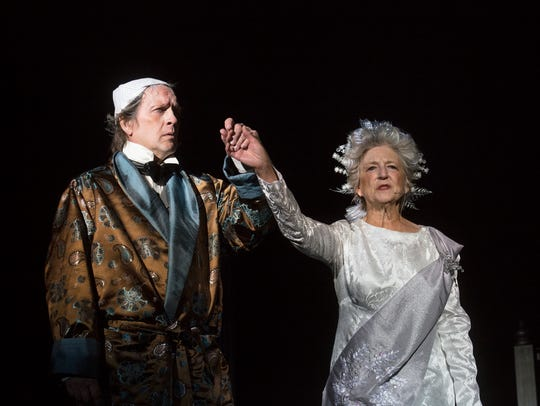 Ebenezer Scrooge, played by Joel Irvin, is led on stage