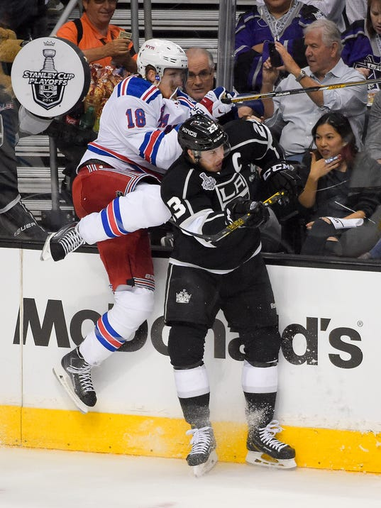 New York Rangers defenseman Marc Staal, left, checks Los Angeles Kings right wing Dustin Brown during the first period in Game 1 of the NHL hockey Stanley Cup Finals, Wednesday, June 4, 2014, in Los Angeles. (AP Photo/Mark J. Terrill)