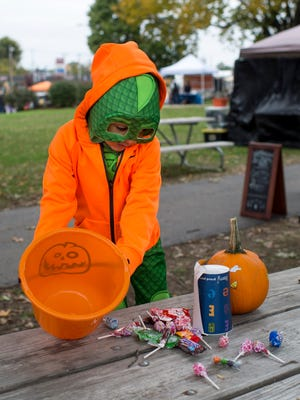 Noah Flemming, 4, dumps out his trick-or-treat loot during Halloween on Franklin at the West Branch Library in Evansville, Ind., on Saturday, Oct. 28, 2017. The event, in its fifth year, is organized by the Franklin Street Events Association and hosted 30 vendors and free activities for kids including hay rides and pumpkin decorating.