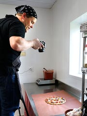 Poco Pizza owner Shawn Pollack takes a photo of a gyro