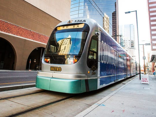 A light rail train pulls out of the station heading