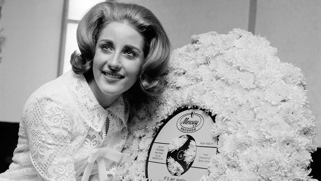 "FILE - In this May 5, 1964, file photo, singer Lesley Gore hugs a flowered record at her 18th birthday party celebrated at the Delmonico Hotel in New York. Singer-songwriter Gore, who topped the charts in 1963 with her epic song of teenage angst, ""It's My Party,"" and followed it up with the hits ""Judy's Turn to Cry,"" and ""You Don't Own Me,"" died of cancer, Monday, Feb. 16, 2015. She was 68. (AP Photo/Marty Lederhandler, File)"