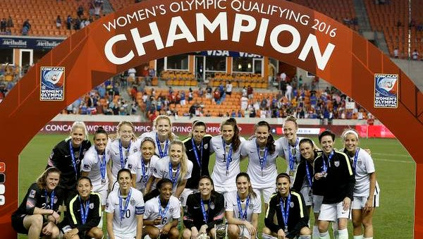 Ashlyn Harris, top row, far left, and the USA team pose with the   championship trophy after USA defeated Canada in the 2016 CONCACAF women's Olympic soccer tournament at BBVA Compass Stadium. USA won 2-0.