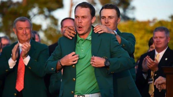 Jordan Spieth helps Danny Willett with his green jacket on Sunday night.