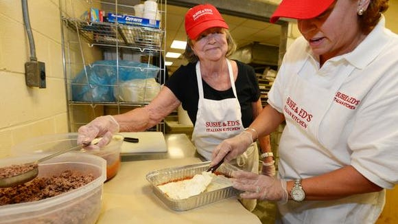Sandra Berardinelli, left, and Tina Cody Berardinelli, right, of Susie & Ed's Italian Kitchen, a company that prepares Italian dishes to be baked at home, prepare a lasagna Tuesday, September 23, 2014.