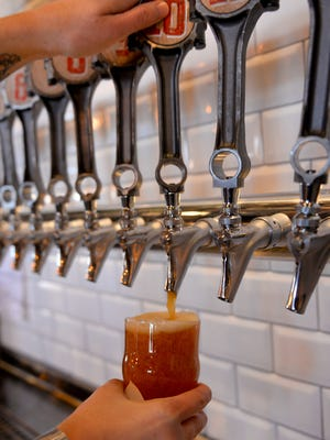 Engine piston rod-handled beer taps as the beer flows at the grand opening of the Lansing Brewing Company in the Stadium District Thursday 10/22/2015