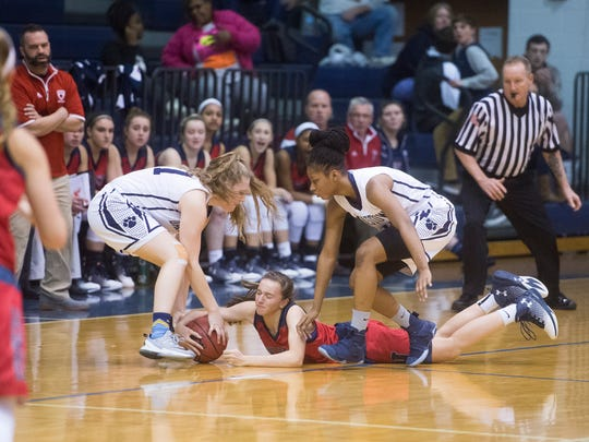 New Oxford's Daelyn Stabler, center, fights for the ball with Dallastown's Sabria Royal, right, and Sabrina Stough during play on Tuesday, Jan. 24, 2017. Dallastown defeated New Oxford 59-47.