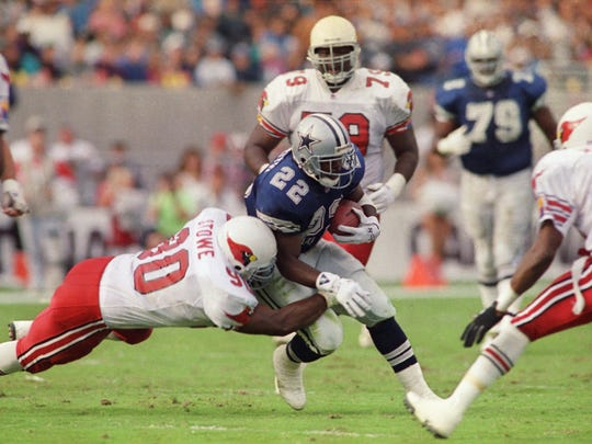 Dallas Cowboys running back Emmitt Smith (22) pulls away from Phoenix Cardinals linebacker Tyronne Stowe on Nov. 23, 1992 in Tempe.