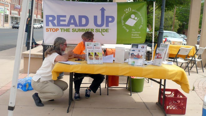 Biorder Partners volunteer Kara Naber, left, chats with Anne Chrestman at the Children's Reading Foundaton of Luna County table during Saturday's Give Local - Give Grandly event at Leyendecker Plaza.