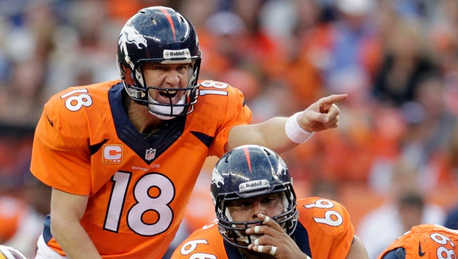 FILE - In this Oct. 27, 2013, file photo, Denver Broncos quarterback Peyton Manning (18) calls an audible at the line of scrimmage  in the fourth quarter of an NFL football game against the Washington Redskins in Denver.