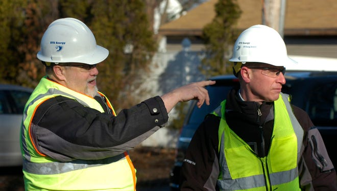 DTE Energy workers Gary Christensen and Joe Robinson point out several problems with trees and wires around a parking lot fence in Birmingham.
