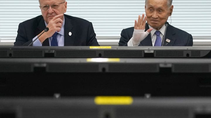 """FILE - In this May 21, 2019, file photo, John Coates, left, chairman of the IOC Coordination Commission for the 2020 Tokyo Olympics and Paralympics, Tokyo Olympic organizing committee President Yoshiro Mori, right, attend the IOC Coordination Commission opening plenary session of the Olympic Games Tokyo 2020 in Tokyo. A top Olympic official has made a guarantee that should please world sports federations that are concerned that organizers of next year's Tokyo games might be cutting things that federations view as """"essential."""" (AP Photo/Eugene Hoshiko, File)"""