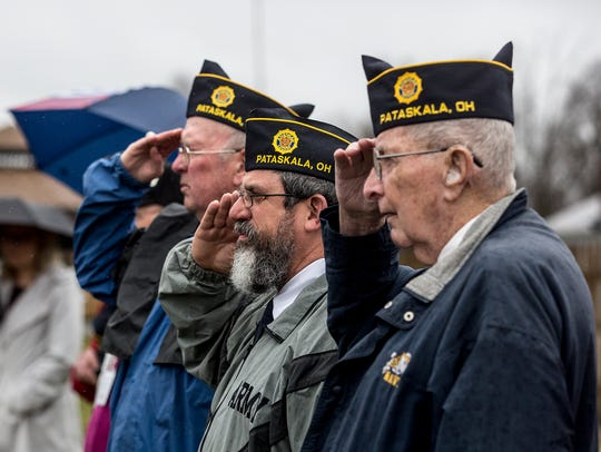 Local veterans salute during the singing of the National