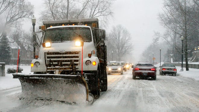 A city snowplow clears snow from southbound lanes during rush hour on North Meridian Street.