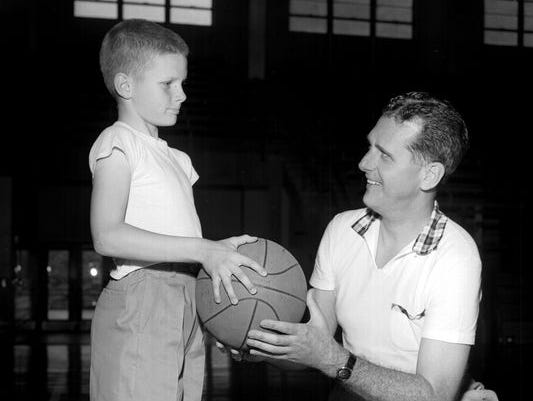 Memphis State Basketball School coach Bob Vanatta (right) helps an enrollee in a youth basketball camp, 11-year-old Ricky Ferguson, on May 9, 1957. Vanatta died Saturday at 98.