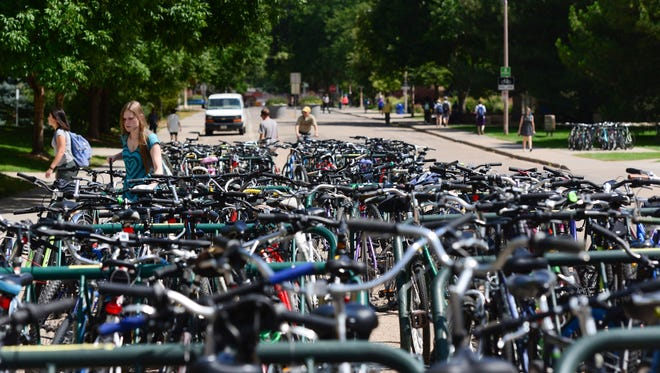Shannon Lovett locks up her bike in a sea of other bikes in front of Lory Student Center Monday, August 29, 2016. CSU now has more than 15,000 bicycle parking spaces on campus.