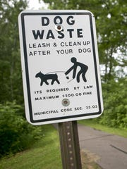 A sign urging owners to pick up after their dog is seen on the Ahdawagam Blue Trail in Wisconsin Rapids.