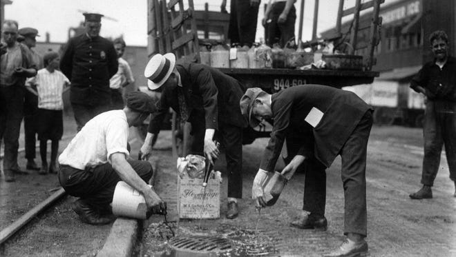 Rochester police property clerk Joseph Sheridan (right) led the pouring as illegal booze was dumped into a gutter during a Prohibition raid on a speakeasy in northeast Rochester. Stone negative collection, Rochester Museum & Science Center.