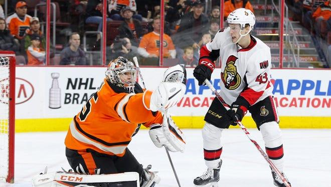 The Flyers' Steve Mason (35) makes a glove save as Ottawa's Ryan Dzingel (43) looks for the rebound.