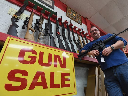 Steve Kottman, general manager of Crazy Louie's Pawn Shop in Salisbury, talks about how more people have been selling their guns, while holding an AR-15 rifle Friday, Dec. 22, 2017.