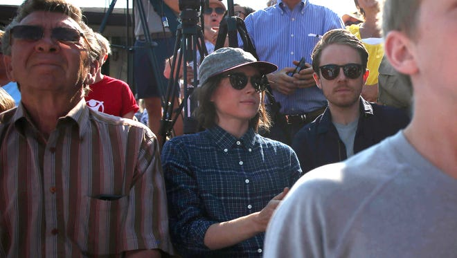 Actress and activist Ellen Page sits among the crowd of supporters who arrived to hear from Republican presidential candidate Ted Cruz on Friday, Aug. 21, 2015, at the Iowa State Fair in Des Moines, Iowa. Page later hit Cruz with questions about gay rights as he was flipping pork chops at the Iowa Pork tent.