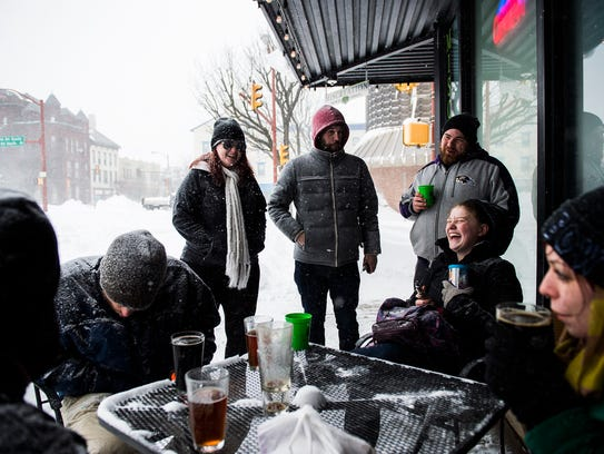 A group of patrons enjoy drinks outside in Center Square