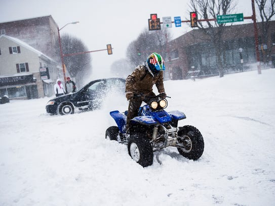 An ATV rider sprays snow into the air before taking